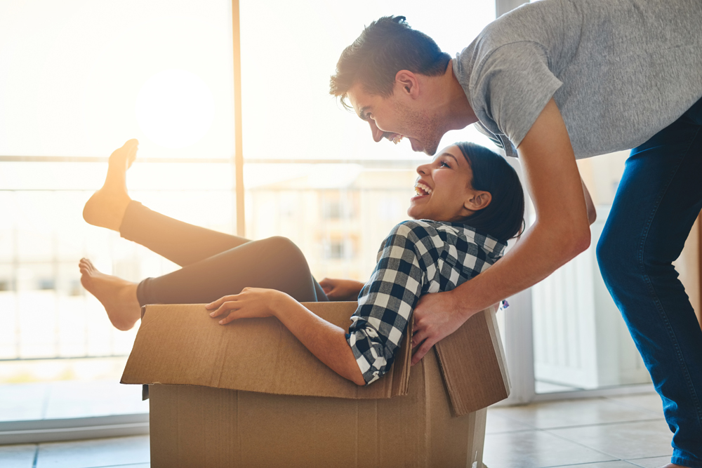 Shot of a young man pushing his girlfriend around in a box while they move into their new home together